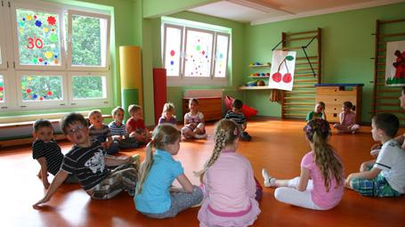 Eine Gruppe Kinder sitzt auf dem Boden.