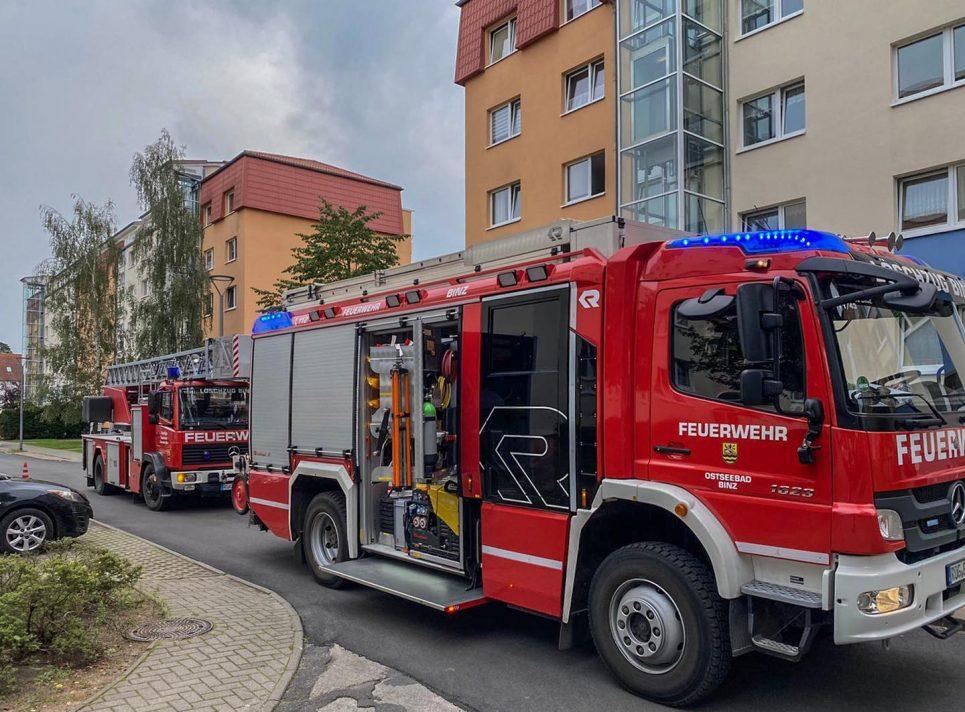 Zwei Einsatzfahrzeuge der Freiwilligen Feuerwehr Ostseebad Binz stehen während eines Einsatzes vor einem Mehrfamilienhaus.
